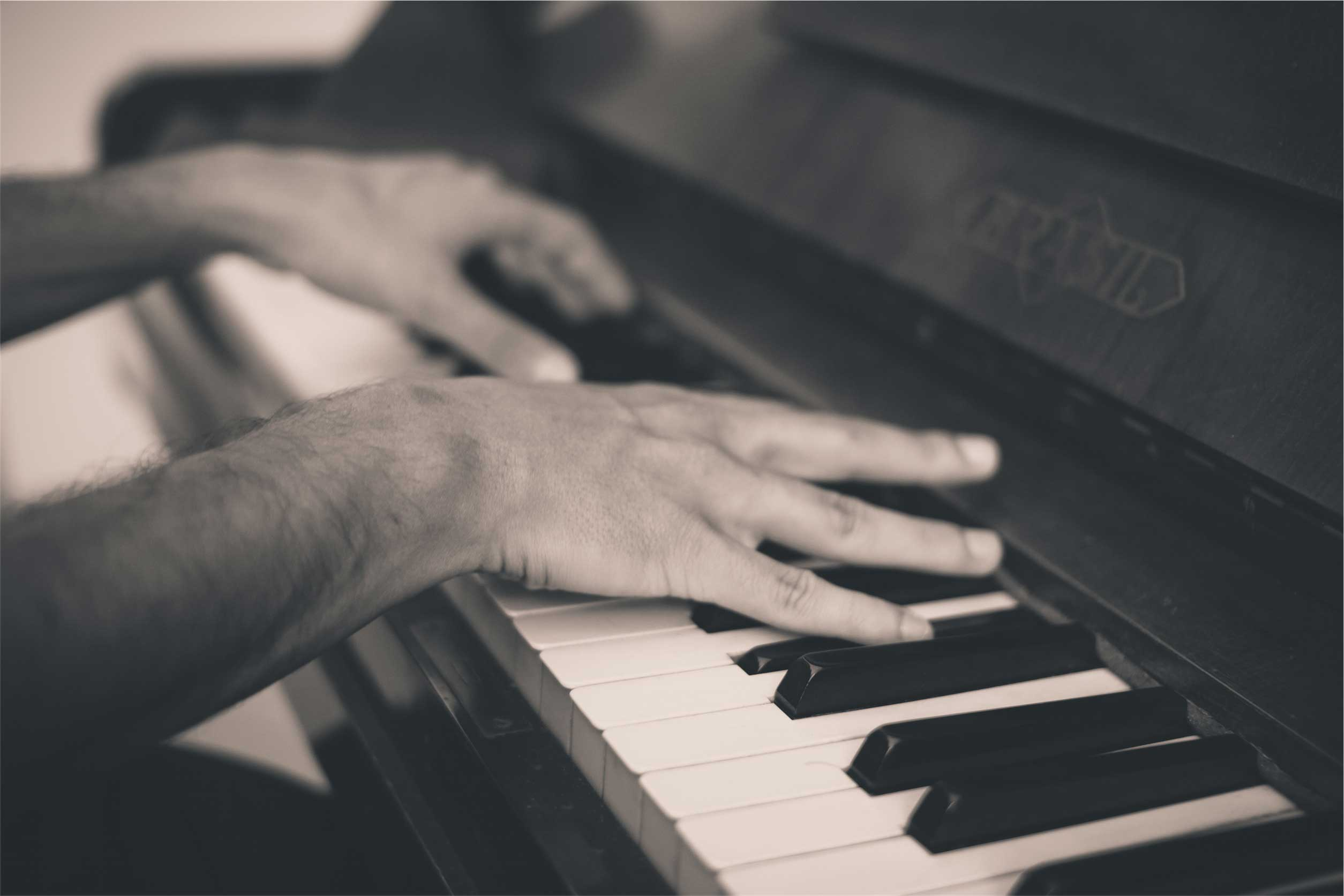 Closeup of hands playing a piano