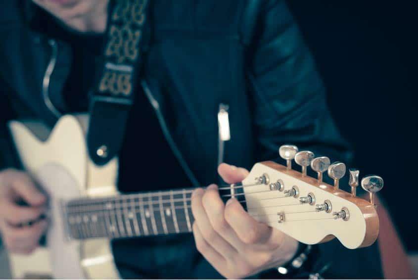 Guitar Technician tuning up guitar in closeup shot