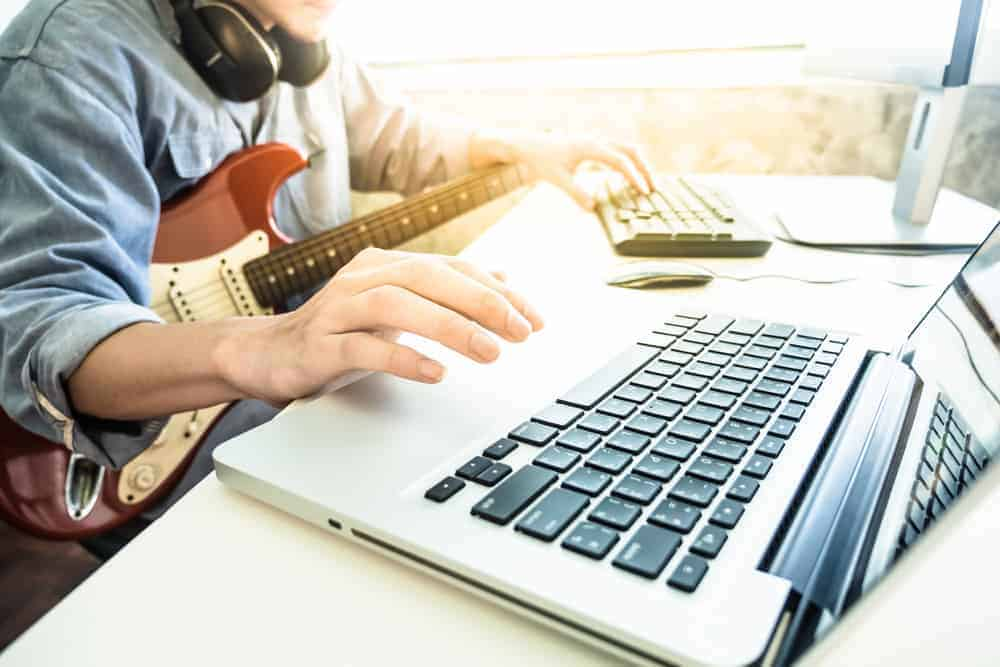 Guitar player with instrument and headphones on laptop