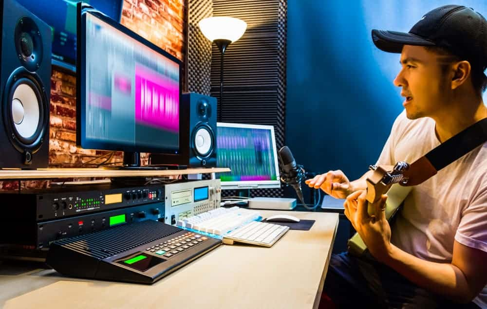 Male guitarist recording electric guitar track in home studio