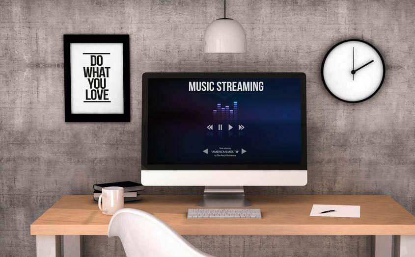 Music streaming website displayed on large desktop computer in modern workspace