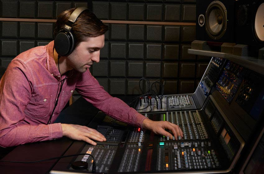 Mastering engineer using mixing console in recording studio