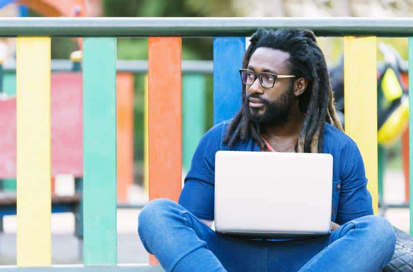 Young man with dreadlocks sitting outside on his laptop