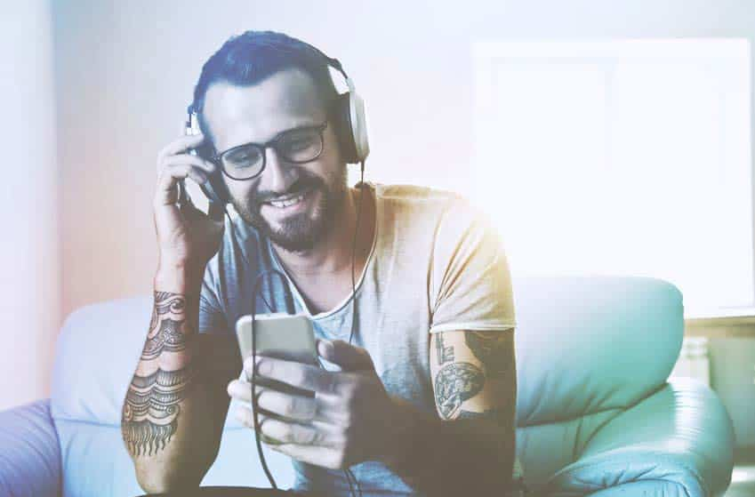 Tattooed young man listening to music on his phone through headphones