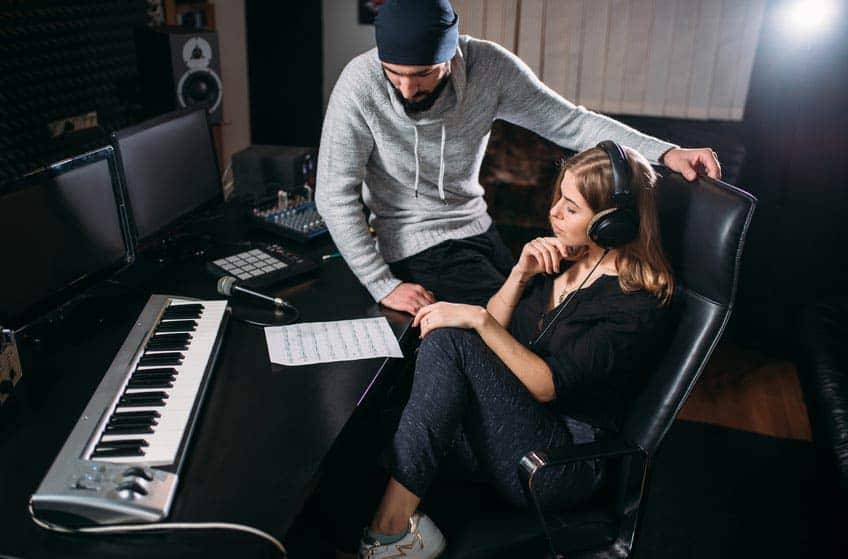 DIY music producers listening to music on headphones in home recording studio