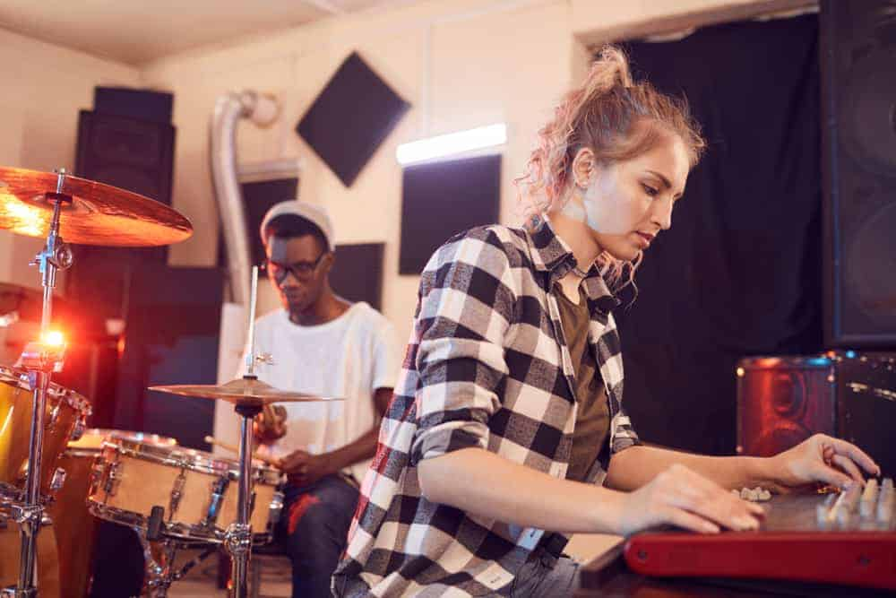 Drummer and keyboard player in rehearsal space