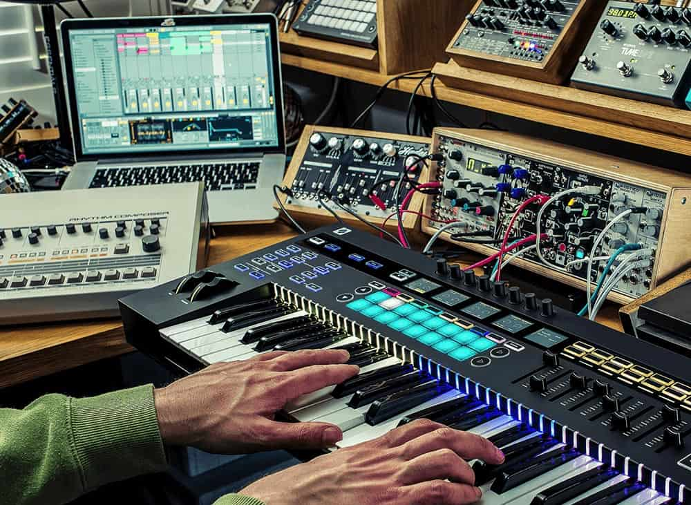 Hands playing Novation keyboard with daw and eurorack