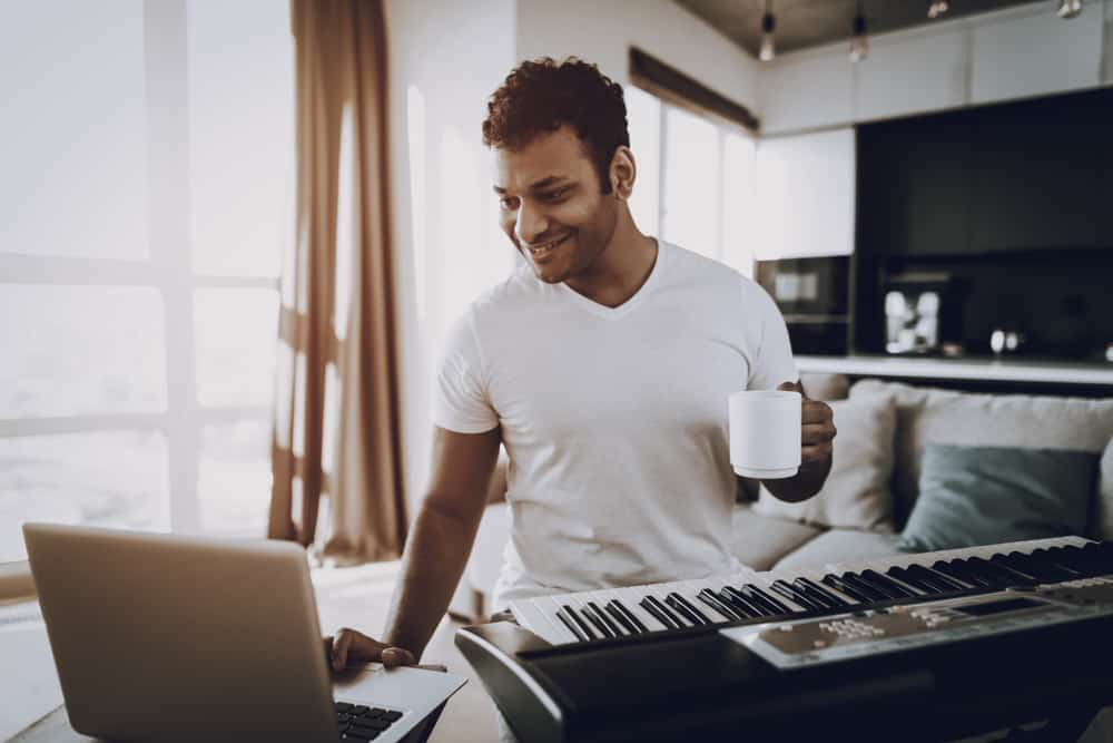 Male musician using laptop to record his keyboard at home