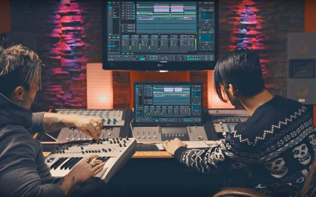 Musicians using digital audio workstation and synthesizer in recording studio