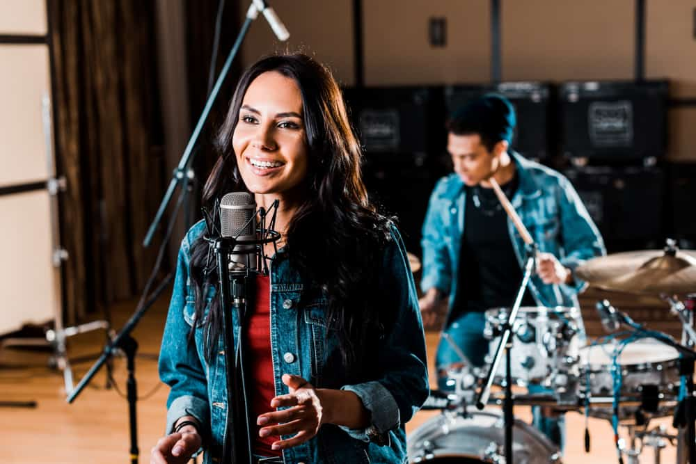 Female singer with condenser mic in studio with male drummer