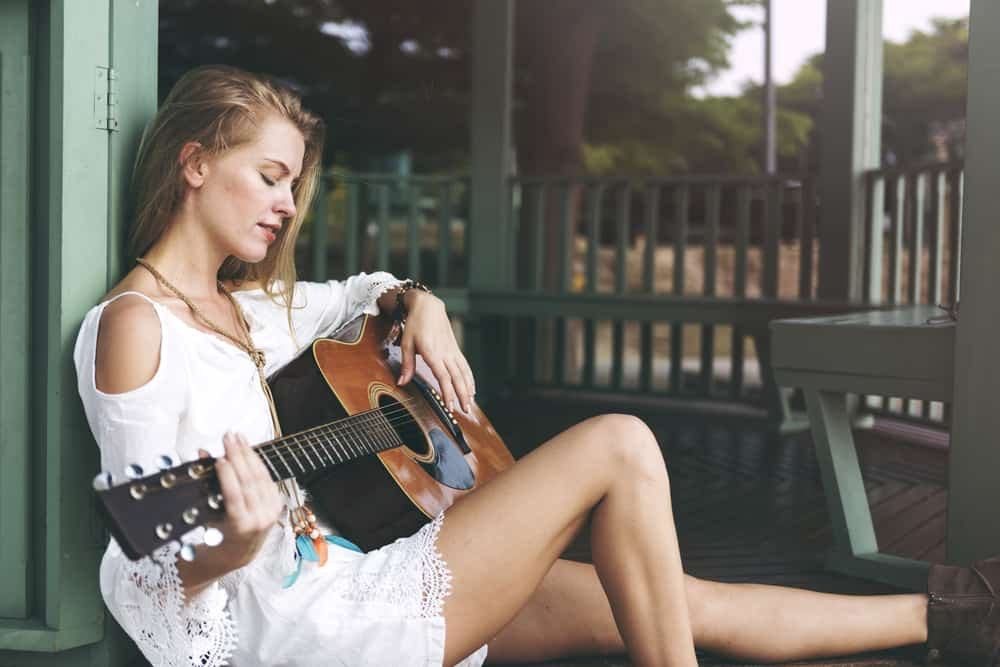 Songwriter playing guitar on her porch