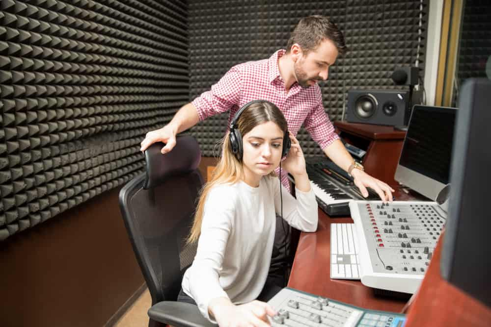 Young audio engineers working together in recording studio