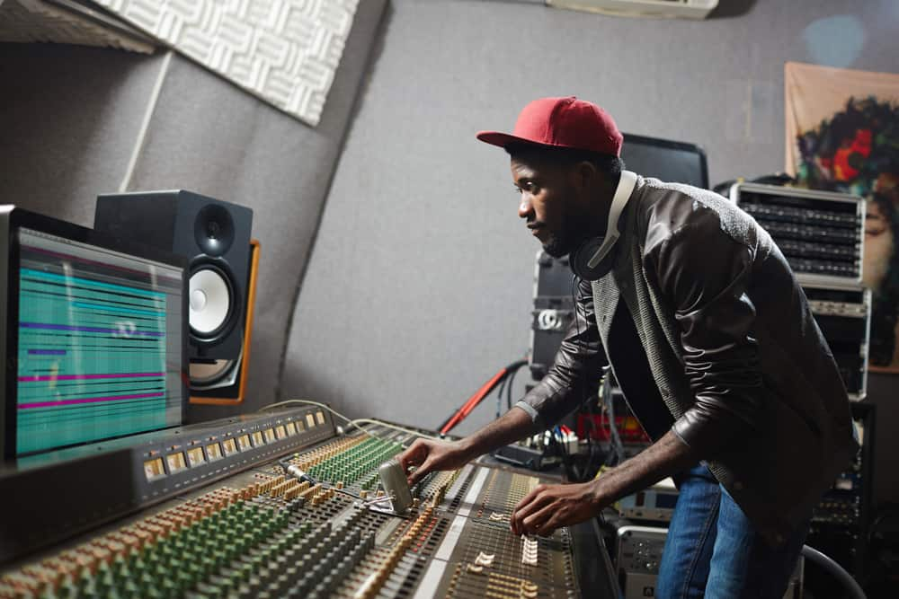 Music producer behind mixing console in recording studio