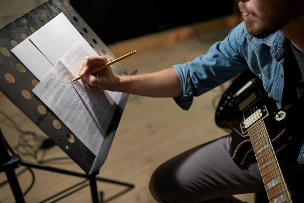 Male guitar player writing on sheet music