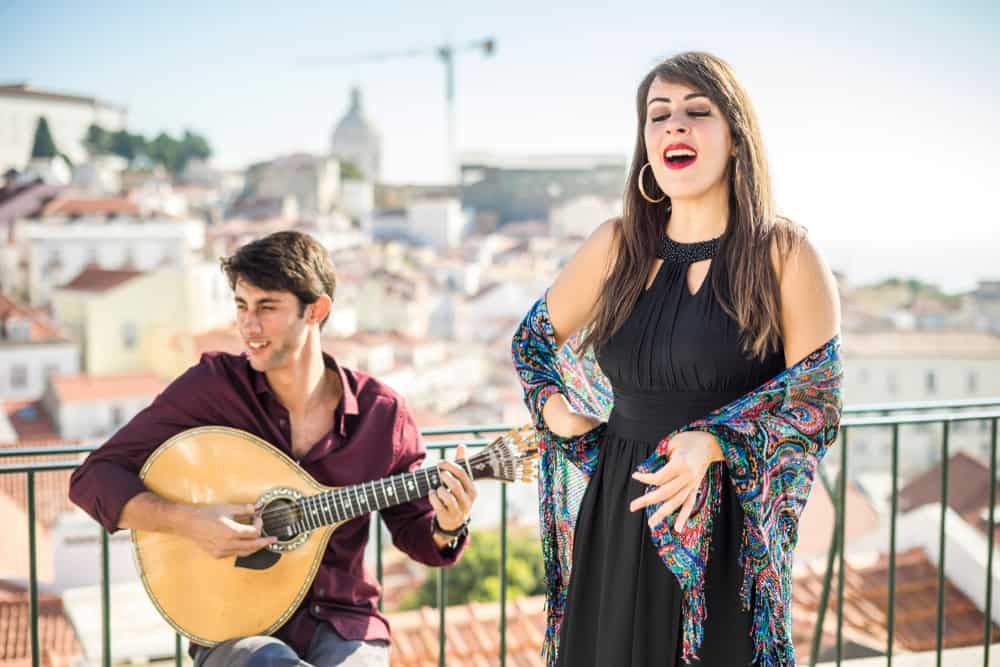 Female singer with male musician and stringed instrument performing outdoors