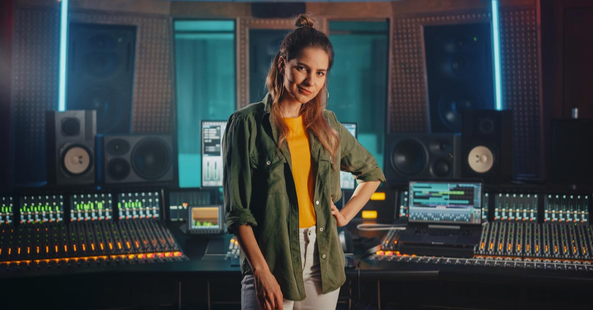 Young female Audio Engineer with soundboard in recording studio